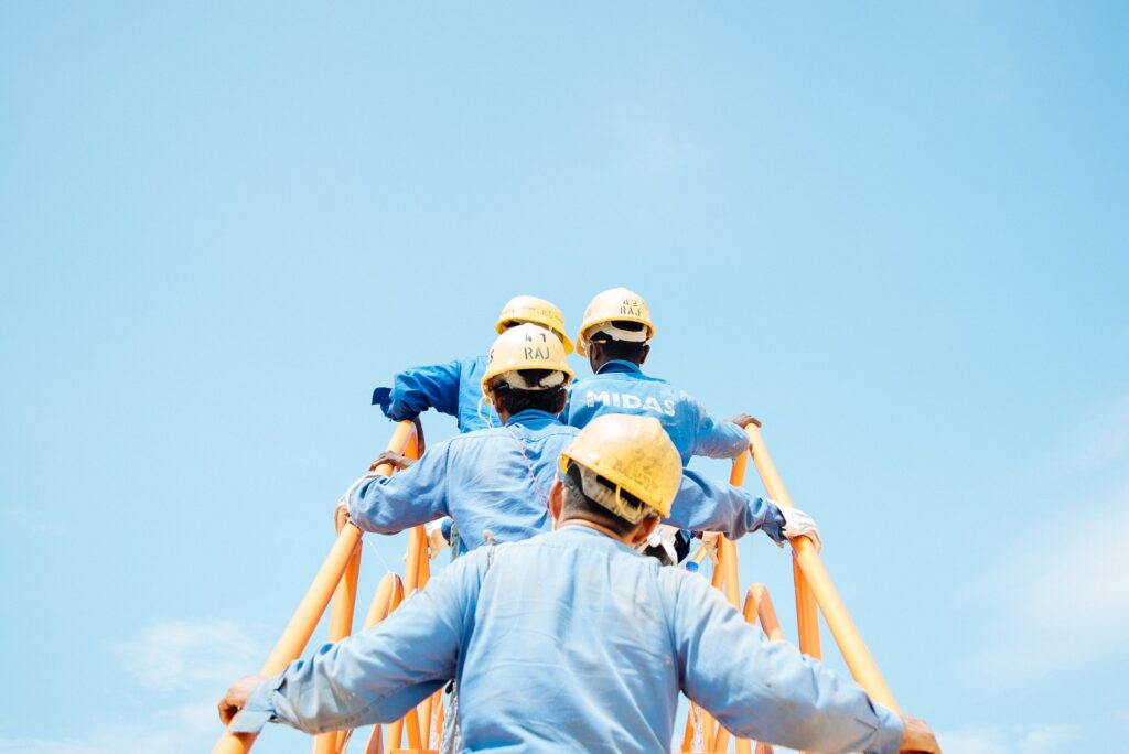 contractors on ladder - hiring remotely often means hiring contractors, and not the construction kind.