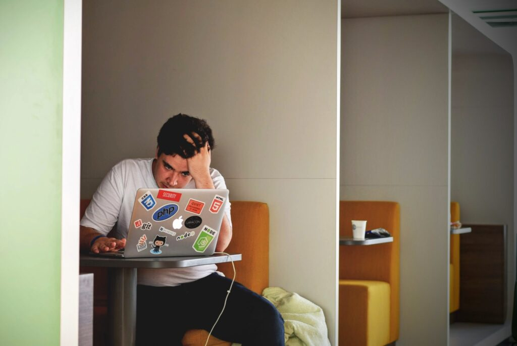 Shows a man stressed whilst working remotely in a coworking space, worried about mental health